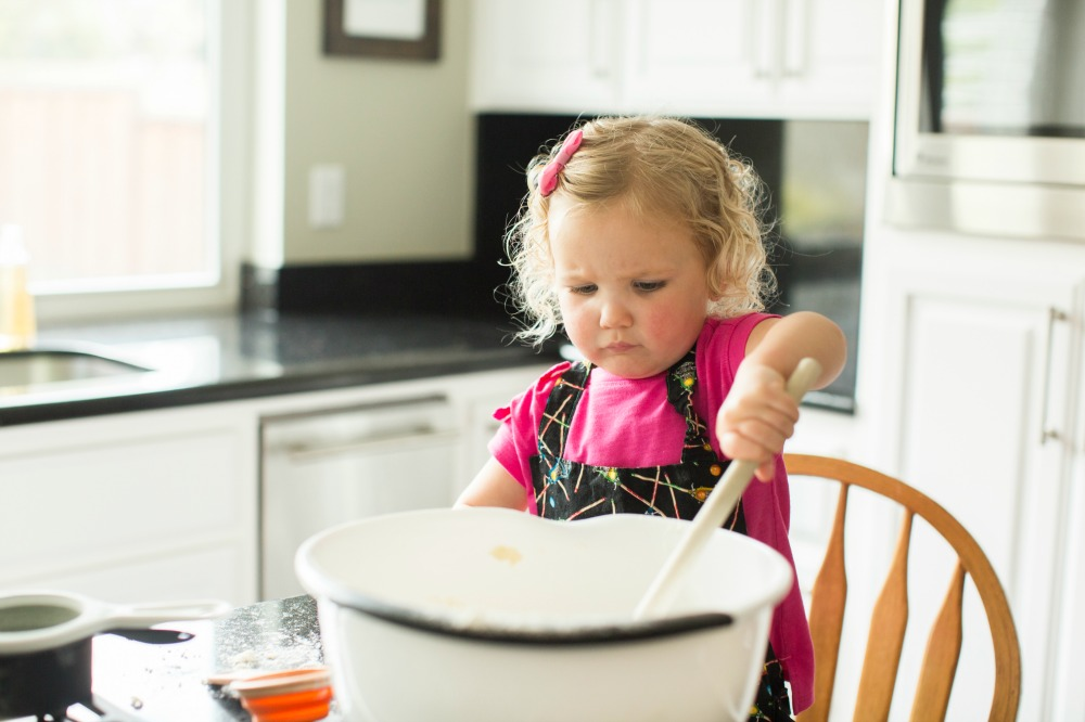 Toddler with large mixing bowl and spoon for cooking activity from Virtual Book Club Summer Camp