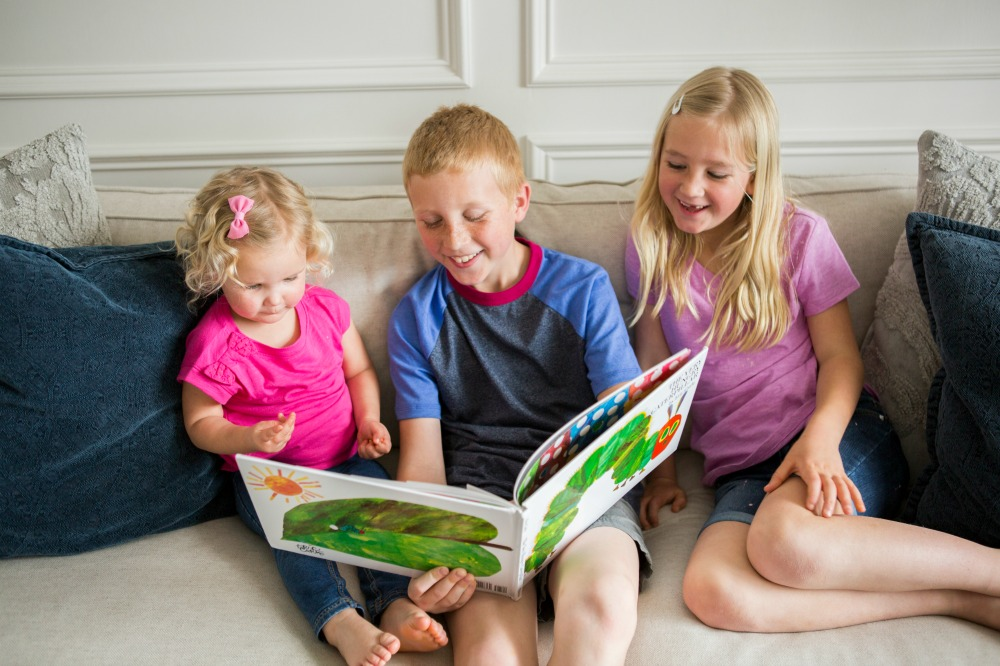 Siblings reading book on sofa for Virtual Book Club Summer Camp