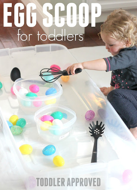 Toddler scooping plastic easter eggs for fine motor activity
